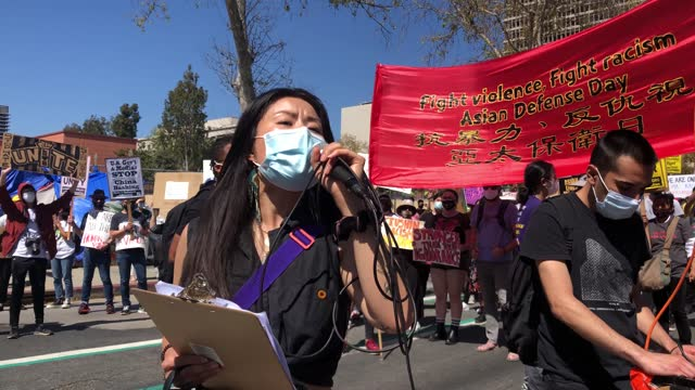 """speaker leads the crowd to chant """"the people united will never be defeated"""" during a demonstration against anti-asian violence and racism through... - asian and indian ethnicities stock videos & royalty-free footage"""