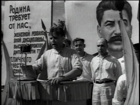 speaker on stage banner of stalin behind / crowd listening / speaker at podium / crowd cheering