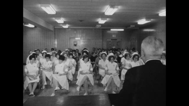speaker talks to assembly of nurses possibly nursing students seated in chairs in uniforms with caps take notes - nurse cap stock videos & royalty-free footage