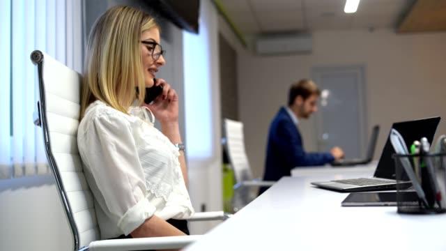 同僚が一生懸命働いている間に電話で話すこと - 椅子点の映像素材/bロール