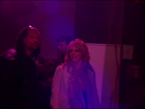 MS Spears walks into club followed by security in BG camera lights flick on