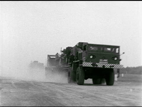 Special Army jointed truck w/ two cabs front rear transporting M65 Atomic Cannon on road HA WS ABOVE Gun on transport turning off road AERIAL OVER...