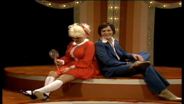 Special guest Jim Stafford approaches Dolly Parton who sits on stage dressed as a little girl wearing pigtails and kneehigh socks licking oversized...