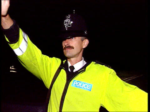 Special look at rave culture in Europe ITN Devon BV Two policemen standing by side of country road as headlights come around corner towards stop as...