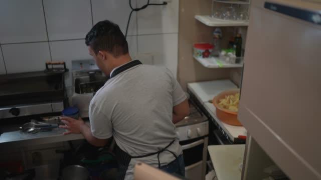 vídeos de stock e filmes b-roll de special needs chef opening the refrigerator in a commercial kitchen - indústria de comidas e bebidas