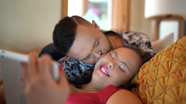 vídeos de stock, filmes e b-roll de pares das necessidades especiais usando a tabuleta digital em casa - beijar
