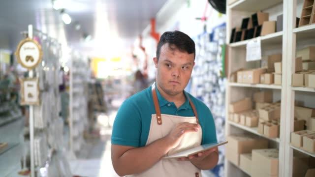 vídeos de stock, filmes e b-roll de funcionários especiais jovens organizando produtos enquanto caminham na loja usando tablet digital - profissão na área de serviços