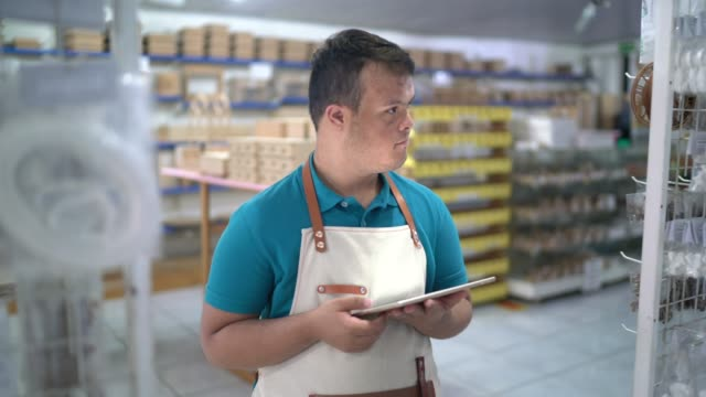 special needs young employee arranging products while walking in the store using digital tablet - disability stock videos & royalty-free footage