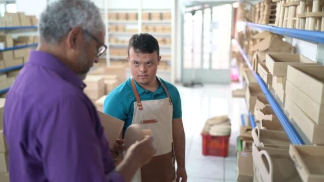 särskild behov ung försäljare bistå en kund i en butik - personer med funktionsnedsättning bildbanksvideor och videomaterial från bakom kulisserna