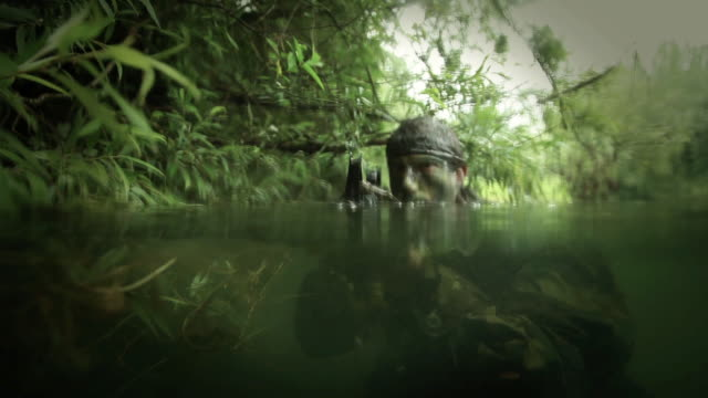 CU U.S. Special Operation Forces rifleman coming out from water with M16 automatic rifle in Vietnam war / Jungle, Hue, Vietnam