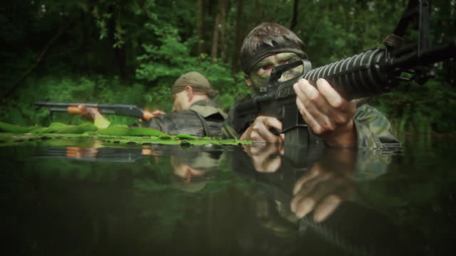 MS TU U.S. Special Operation Forces soldiers in water with automatic rifles and shotgun in Vietnam war / Jungle, Hue, Vietnam
