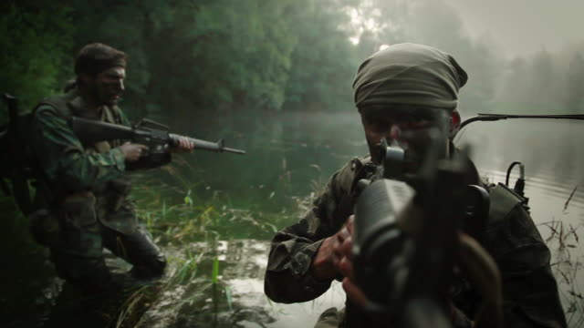 MS POV U.S. Special Operation Forces soldiers with AR15 and M16 automatic rifles walking in river in Vietnam war / Jungle, Hue, Vietnam