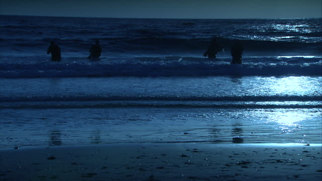 a special ops team exits the surf and approaches a dark beach. - special forces stock videos & royalty-free footage