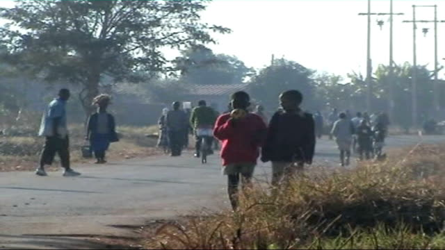 Special report on inflation and poverty ZIMBABWE Harare EXT Township residents along dusty street View of countryside from car window TRACK EXT...