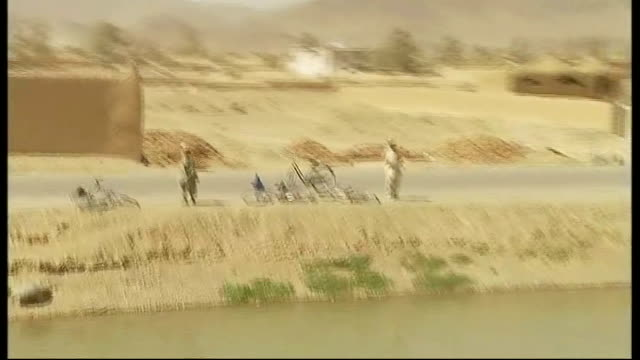 special report on royal dragoon guards in kandahar city; tracking shot past afghan people in river and at roadside tracking shot as man across river... - kandahar stock-videos und b-roll-filmmaterial