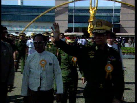 vidéos et rushes de political situation in burma; burma: rangoon: outside aung san suu kyi's house: peephole in gate as cover is lifted to show group of people sitting... - séquence segment monté
