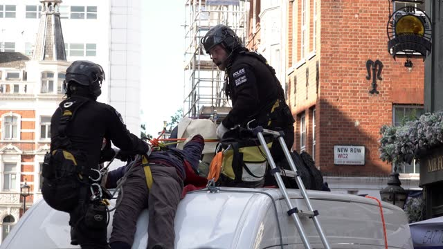 specialist police teams remove and arrest a climate change protestor from the rooftop of a van, which is being used as a road blockade at the... - road stock videos & royalty-free footage