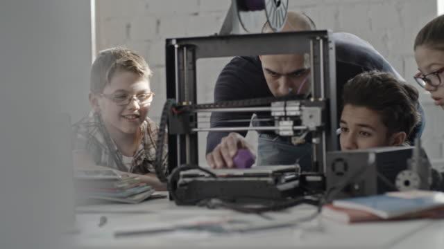 IT specialist showing printed plastic detail to school children
