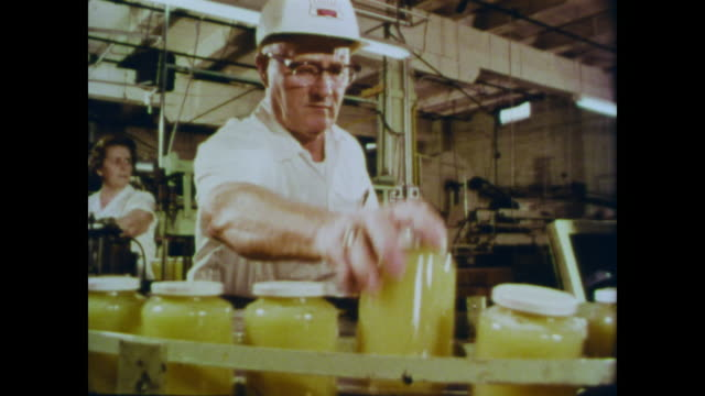 1966 usda specialist tests, weighs, tastes and inspects a jar of apple sauce taken from the factory - sauce stock videos and b-roll footage