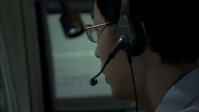 a specialist wears glasses as he views a ship image on a computer monitor. - radio stock videos and b-roll footage