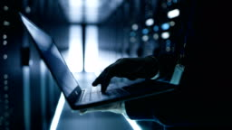 IT Specialist Working Working on a Laptop, He's Employee of  Big Ultramodern Data Center.