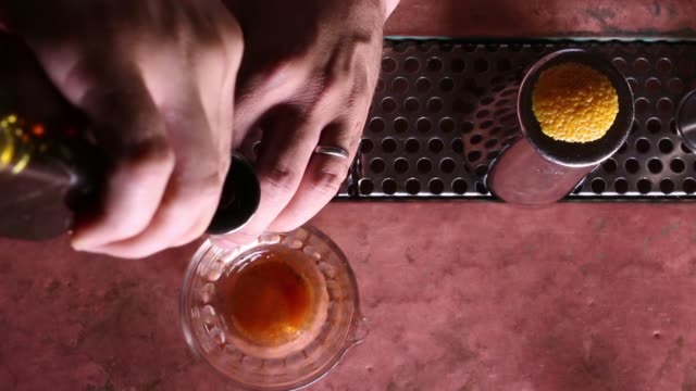 a speciality cocktail is mixed at please dont tell in new york ny us on august 18 shots overhead close ups of a bartender mixing a cocktail close up... - peel stock videos & royalty-free footage