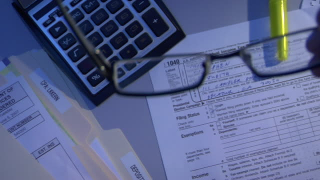 CU, PAN, HA, Spectacles and 1040 tax form on table at night
