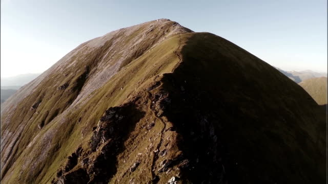 Spectacular aerial shot on Sgurr a'Mhaim mountain revealing devils ridge in the Scottish highlands during sunset