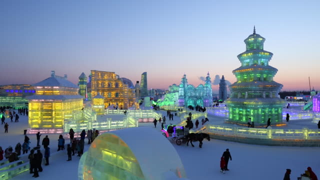 spectacular illuminated ice sculptures at the harbin ice and snow festival in heilongjiang province, harbin, china - schneefestival stock-videos und b-roll-filmmaterial