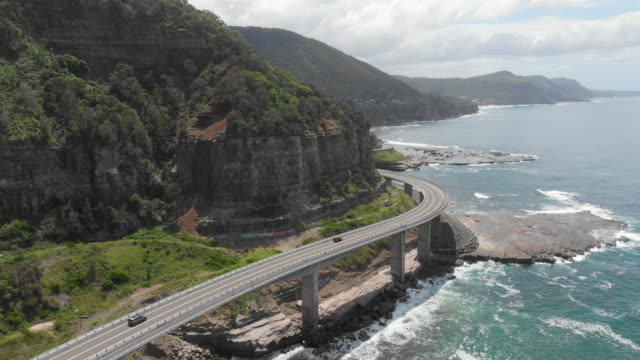 spectacular ocean drive along ocean road along a bridge that carries cars along the coast - ニューサウスウェールズ州点の映像素材/bロール