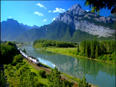 spectacular rocky mountains under bright blue sky train goes along tracks past clear lake banff - banff stock videos & royalty-free footage