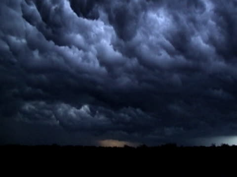 Spectacular supercell thunderstorm with turbulent clouds over rural field.