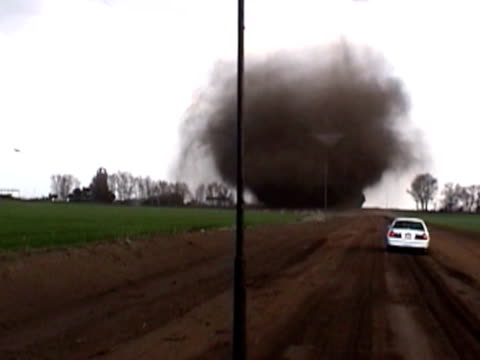 spectacular tornado crosses dirt road just missing state trooper. - kansas stock videos and b-roll footage