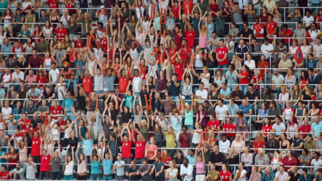 ld spectator crowd performing the wave at a sporting event - winken stock-videos und b-roll-filmmaterial