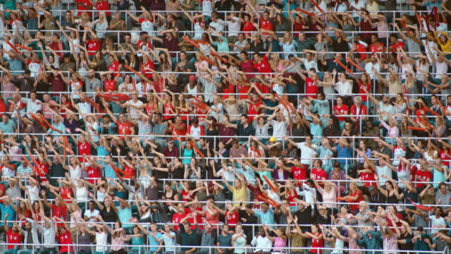 LD Spectator crowd watching a game and cheering on the tribunes at the stadium by moving hands from side to side
