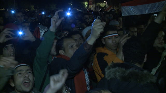 Spectator holding camera in air above chanting crowd during Mubarak's speech in Tahrir Square / Cairo Egypt
