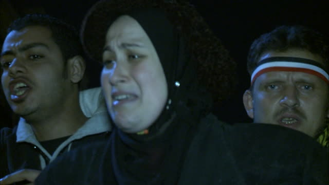 CU Spectator in Tahrir Square upset holding her hands over her face as others are yelling during Mubarak's speech / Cairo Egypt