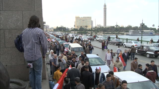 td spectator standing on a ledge next to bridge as passing crowd of pedestrians walks down street by parked cars and waving egyptian flag / cairo... - 2010 stock videos & royalty-free footage