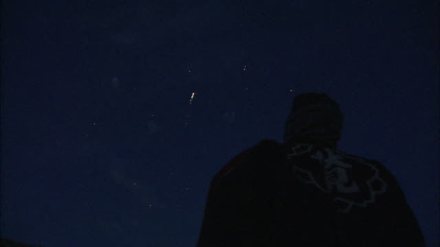 a spectator watches fireworks explode in the night sky. - one night stand stock videos & royalty-free footage