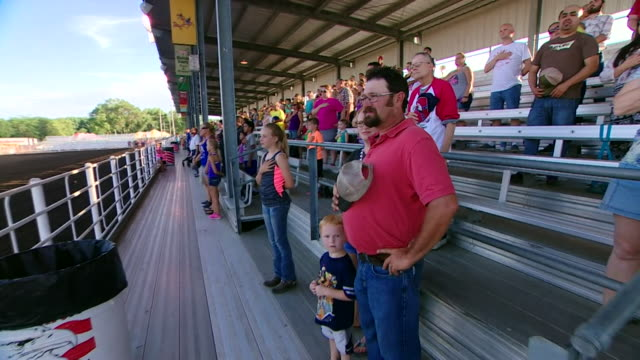 spectators at a county fair in nebraska stand for the national anthem of the usa, 'the star-spangled banner'. - hand aufs herz stock-videos und b-roll-filmmaterial
