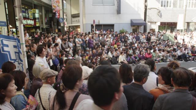 spectators at the koenji bikkuri daidogei festival - street performer stock videos and b-roll footage