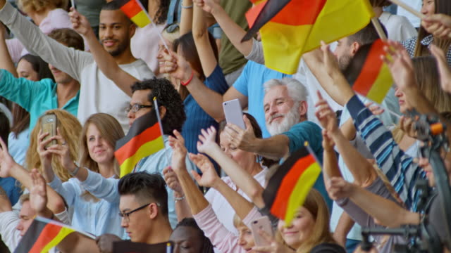 SLO MO Spectators at the stadium waving German flags