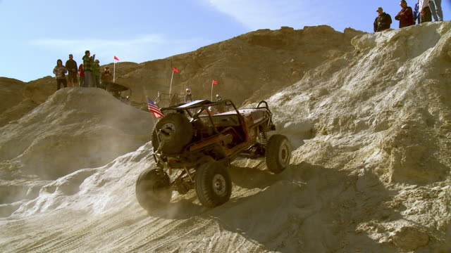 Spectators at the top of a dirt hill in the California desert watch a rock climber try driving a vehicle up the hill.