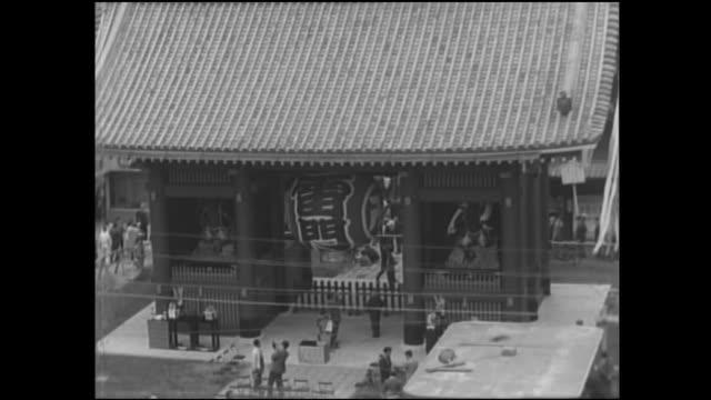 vídeos de stock, filmes e b-roll de spectators bustle through the streets surrounding kaminarimon. - templo asakusa kannon
