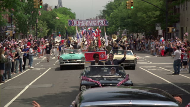 Spectators cheer and wave flags during a Fourth of July Parade.
