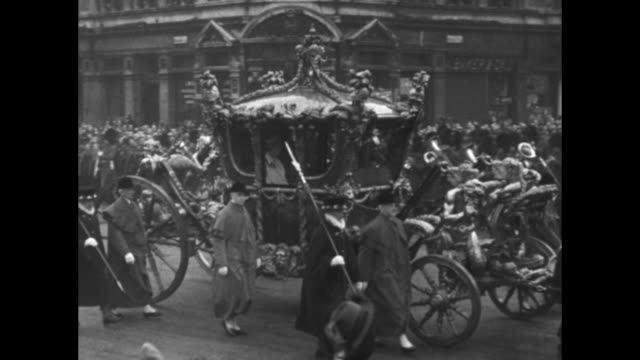 VO spectators cheer as Gold State Coach bearing George V and Queen Mary passes by en route to the Palace of Westminster for the State Opening of...