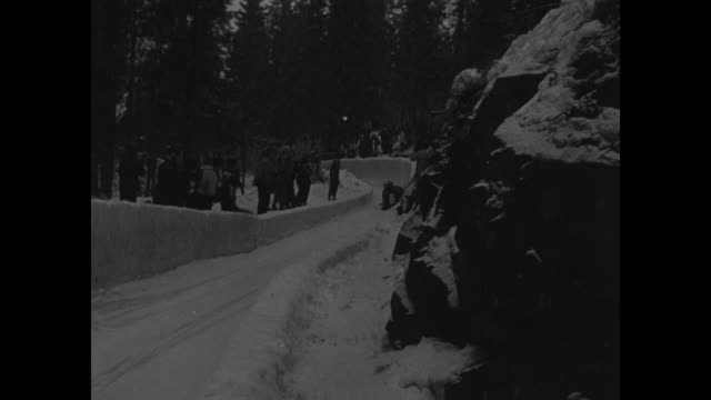 spectators gather at starting line of 1952 winter olympic bobsledding competition / german fourman team ramps up speed before hopping onto sled /... - bobsleighing stock videos & royalty-free footage