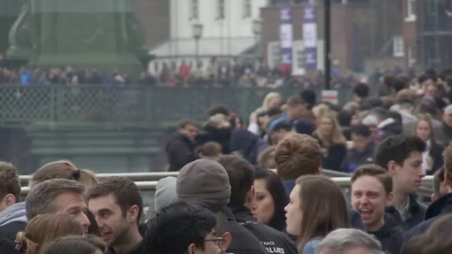 spectators gather at the thames to watch the boat race between oxford and cambridge. - oxford england video stock e b–roll
