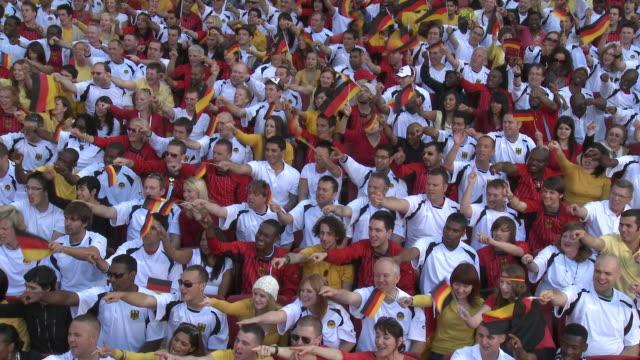 WS Spectators in bleachers cheering and waving German flags, London, UK