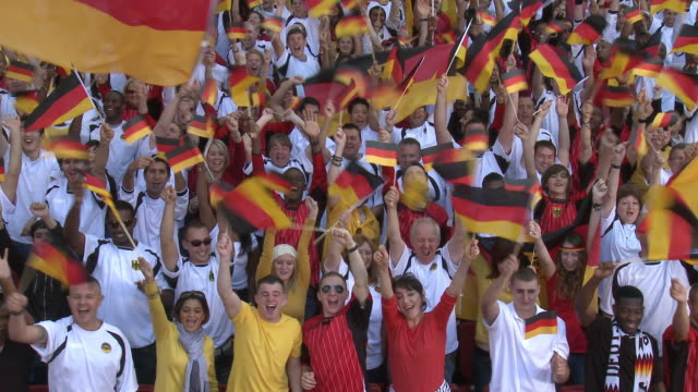 WS Spectators in bleachers cheering and waving German flags, London, UK